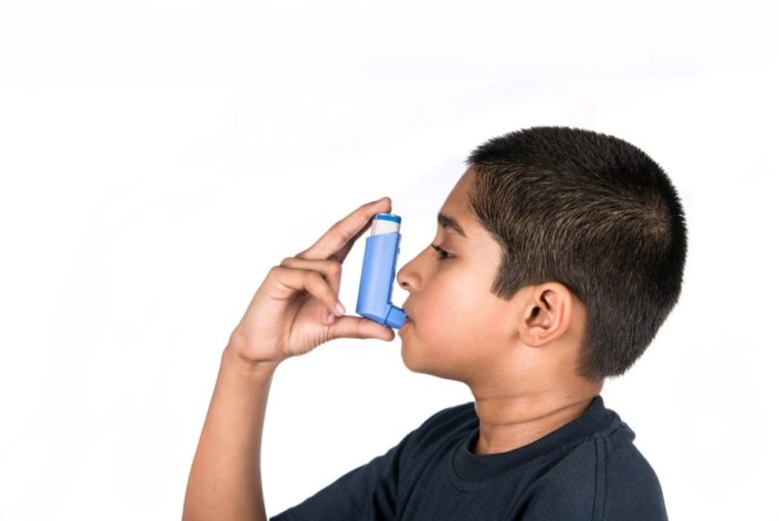 Young boy using asthma inhaler