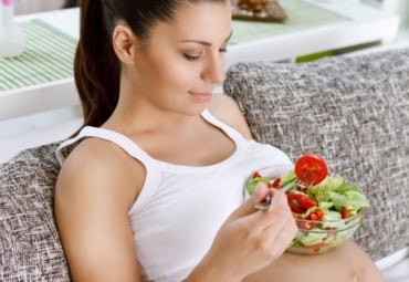 Pregnant woman balancing bowl of salad on belly