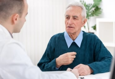 Senior man sitting with doctor, pointing at chest