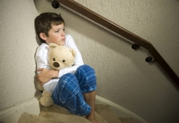 Fearful boy hugging teddy bear