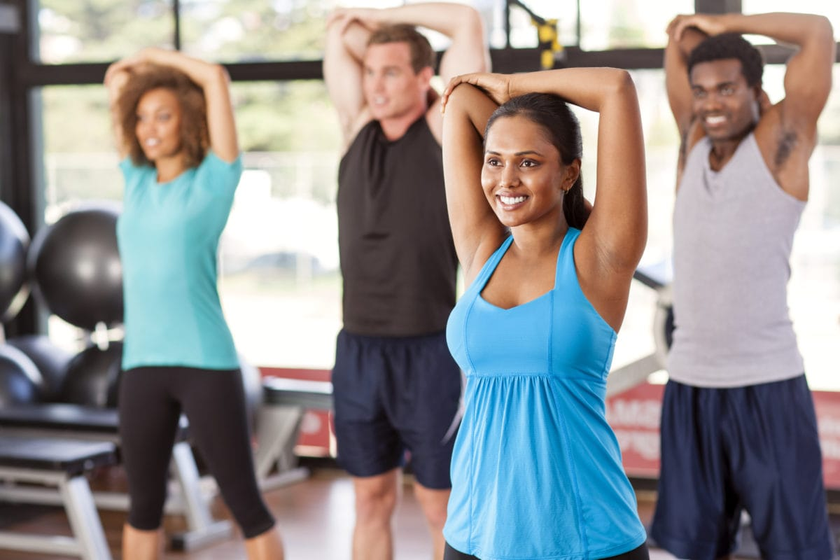 A group of men and women in exercise class doing the same arm stretch