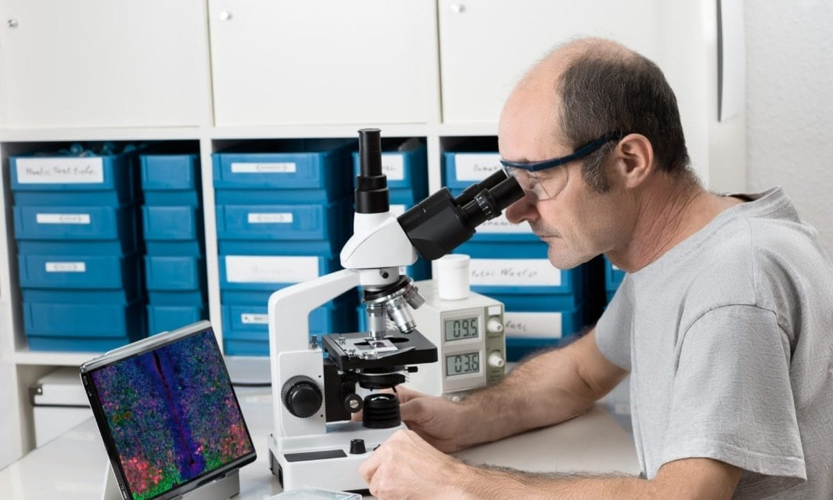 Male scientist or tech observes biopsy sample under a microscope