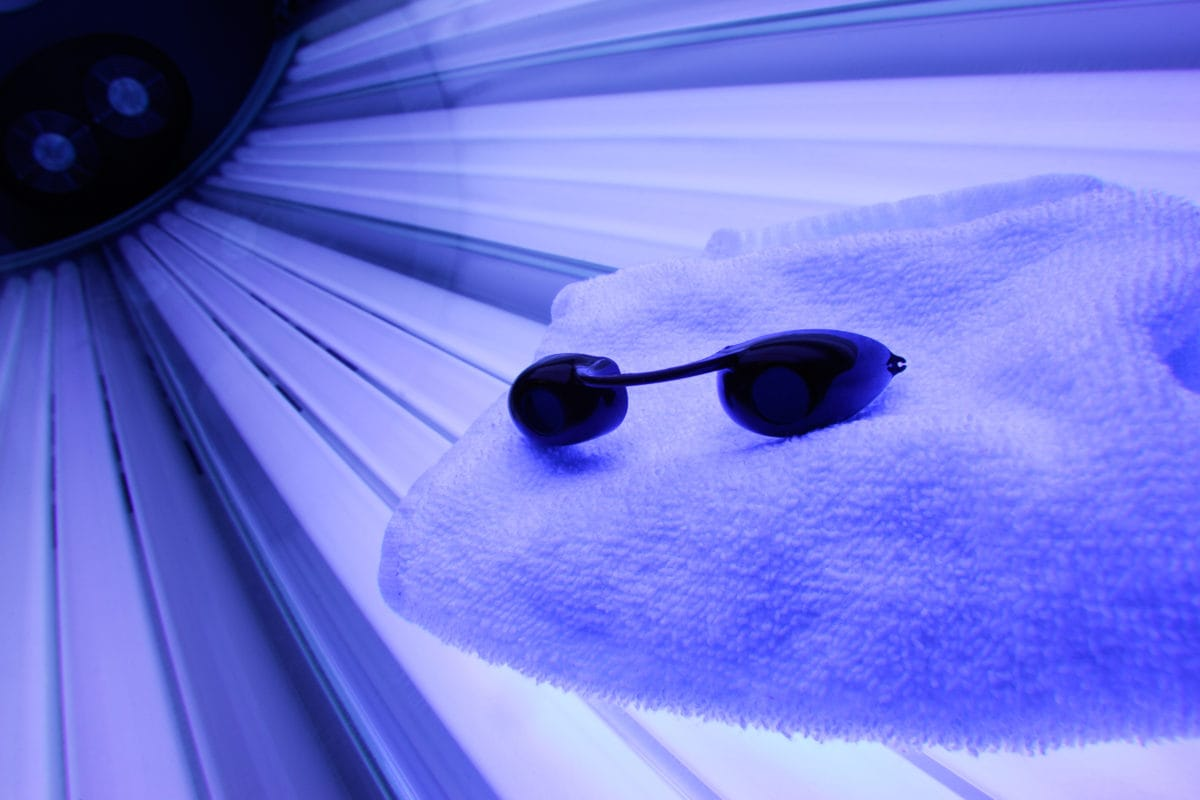 Tanning bed with glasses and towel