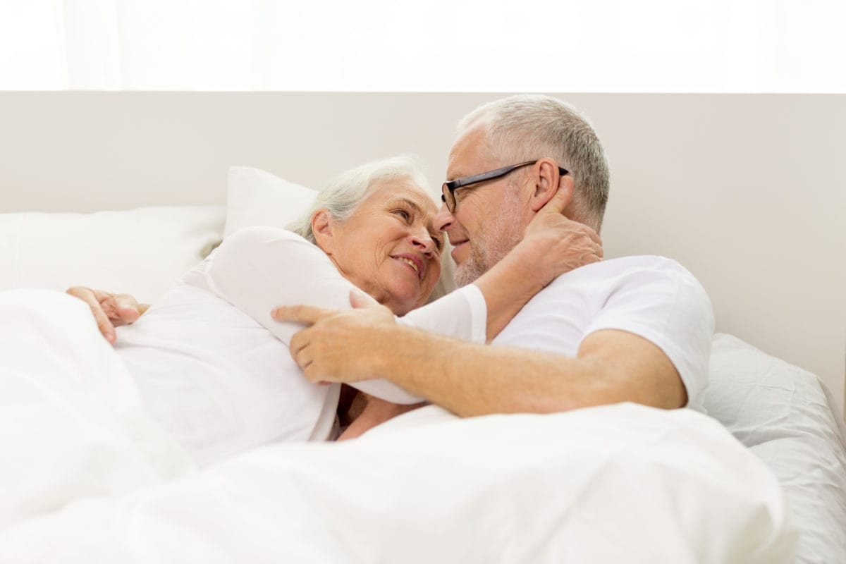 An older couple in bed cuddling