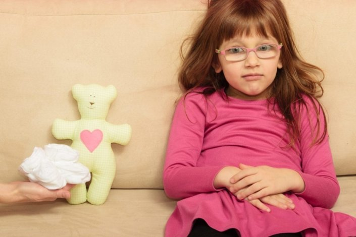 Little girl sitting on sofa next to teddy bear and small shoes for unborn sibling