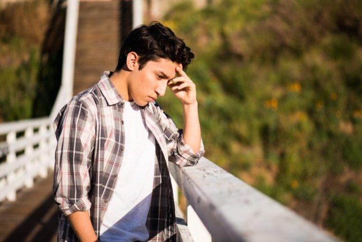 Sad-looking teenage boy standing on a bridge, thinking about suicide