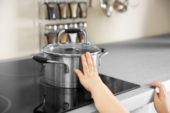 Young child touching hot pot on the stove
