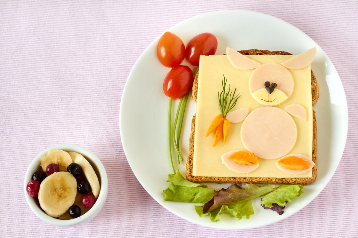 A plate with healthy food cut in the shape of a rabbit with a side cup of fruit