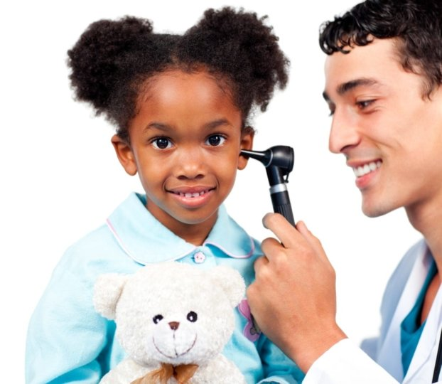 Little girl smiling as doctor examines her ear