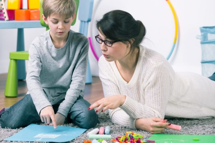 Female therapist working with young boy on floor