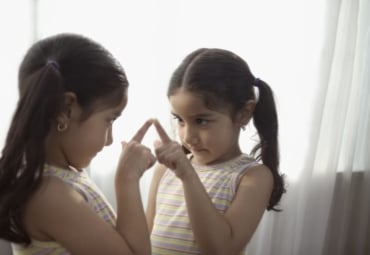 Young girl looking at her reflection in the mirror