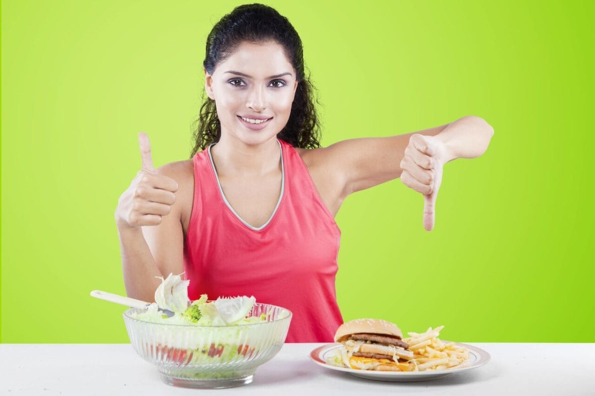 Woman giving thumbs up to salad and thumbs down to burger