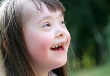 a young girl with Down syndrome looks up and smiles