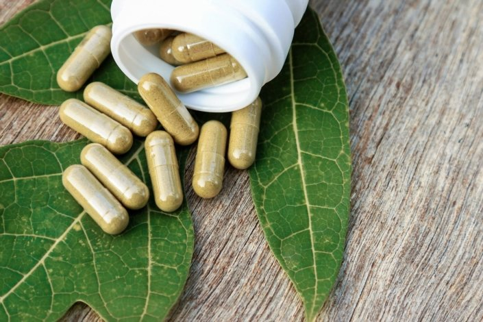 Herbal supplements in capsules spilling out from a white bottle