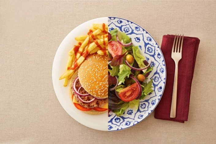 Unhealthy, high-carb burger and fries on one side of the plate and a healthy, low-carb salad on the other side.