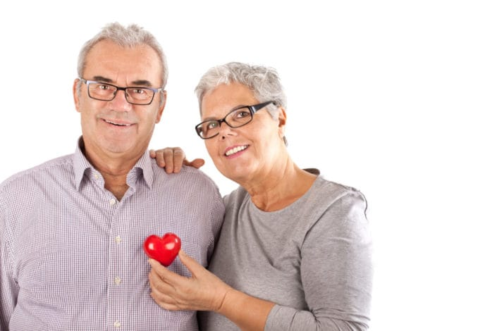 Man and woman standing together with red heart in front
