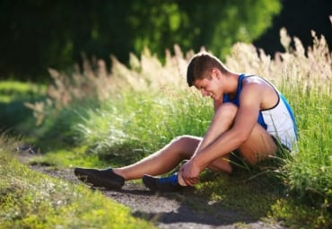 Young male runner holding ankle in pain