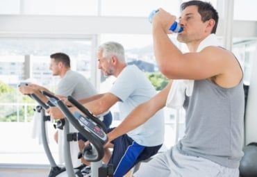 Three men, one of them older, on exercise bikes at gym