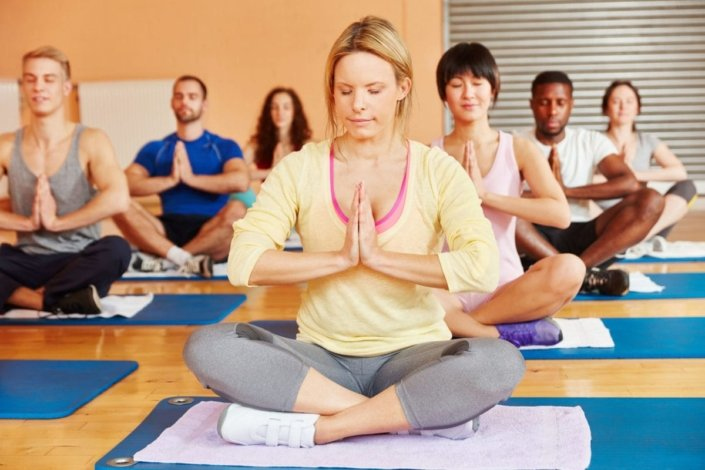 group of young men and women sitting in meditation in a yoga studio