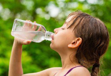 sweaty girl drinking water from a bottle outside