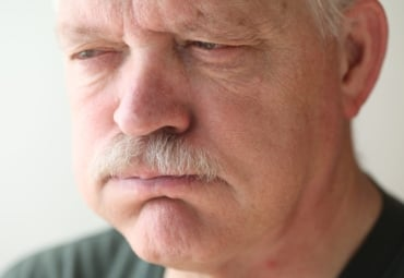 A senior man experiences bloating and reflux from indigestion.