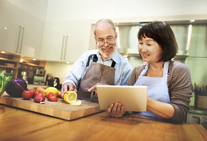 Older couple standing at counter, preparing a meal with healthy fruits and vegetables