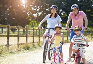 family of four wearing helmets and riding bicycles together