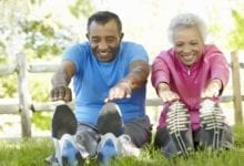 older couple stretching before exercise in a park