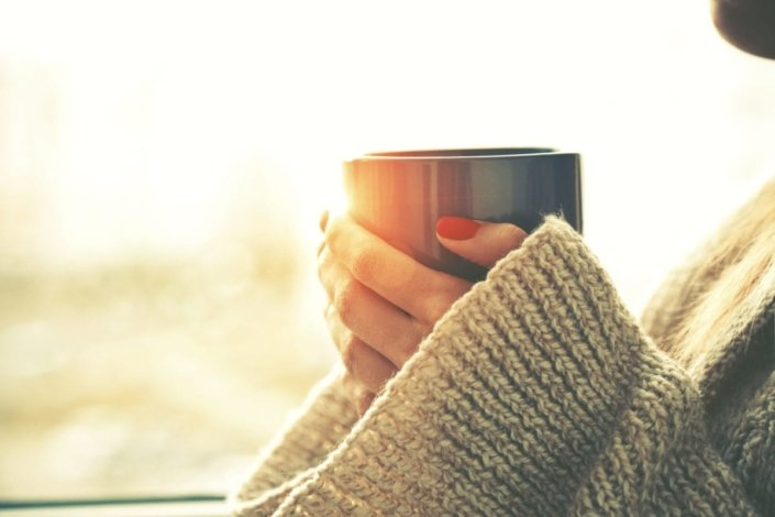 woman's hands holding hot cup of coffee or tea in morning sunlight
