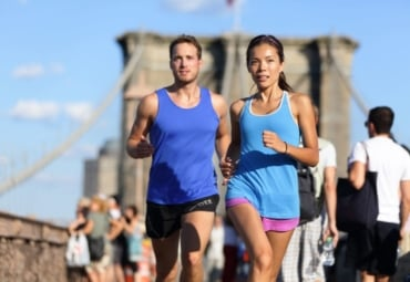 Couple running on Brooklyn Bridge in New York City