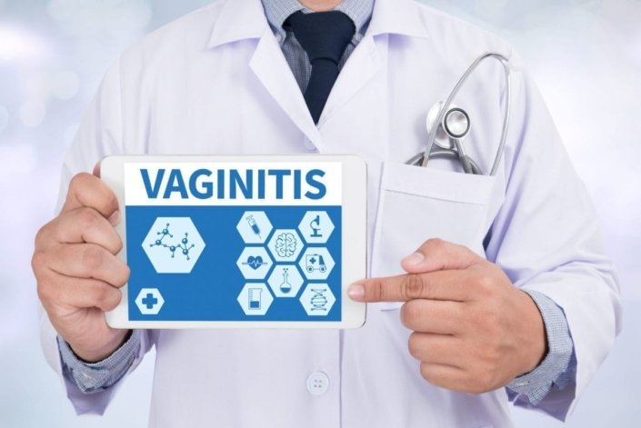 doctor in lab coat holding tablet describing vaginitis