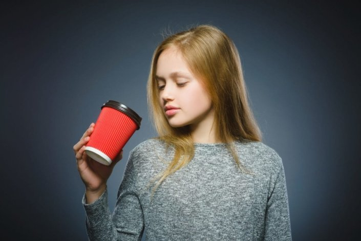 eenage girl sipping from to-go coffee cup