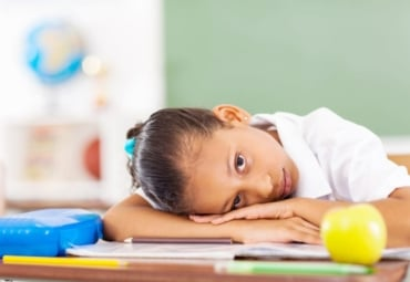 young girl rests her head on her desk at school