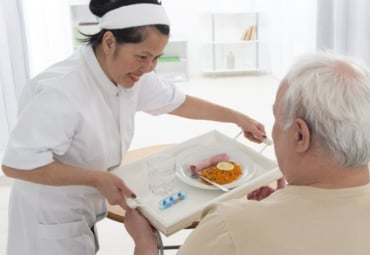 Nurse gives tray of food and medicines to senior man