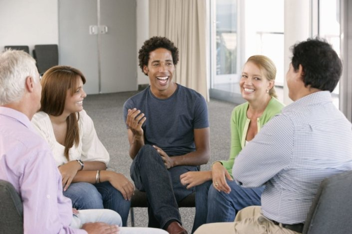 a support group sits in a circle and laughs