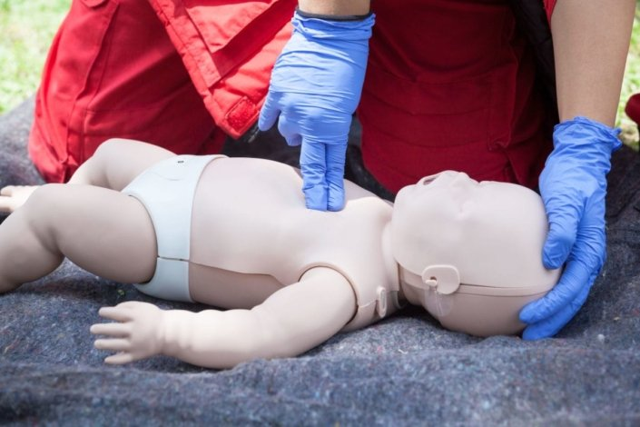 Person doing CPR on baby dummy during first-aid training