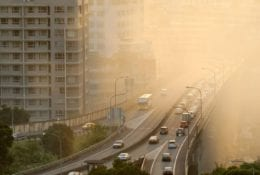 Air pollution scenic with cars on highway and yellow smoke in city