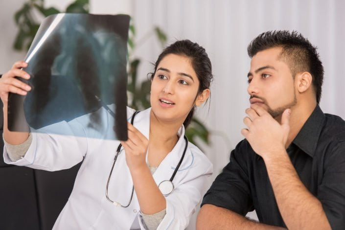 female doctor looks at X-ray with a male patient
