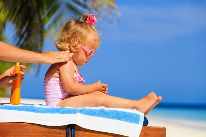 A mother applies sunscreen to her little girl's shoulder at the beach