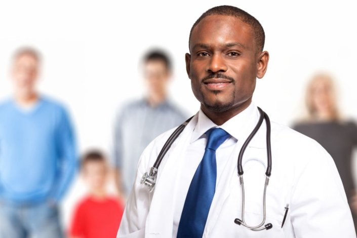 family doctor stands in front of blurred family in background
