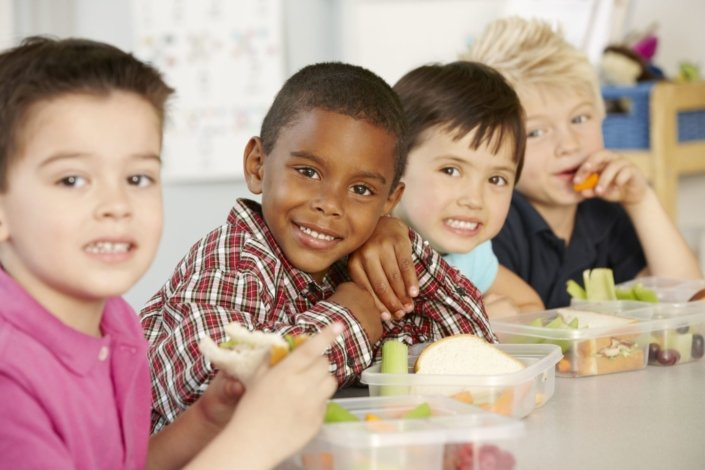 group of young children eating healthy packed lunches at school