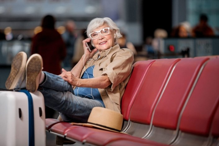 Senior woman with her feet propped up on her suitcase, talking on her cell phone while waiting for her flight