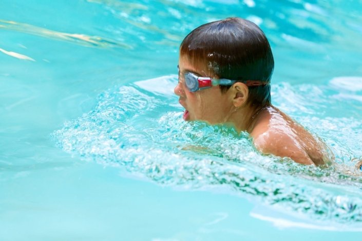 Close up of young boy swimming in pool