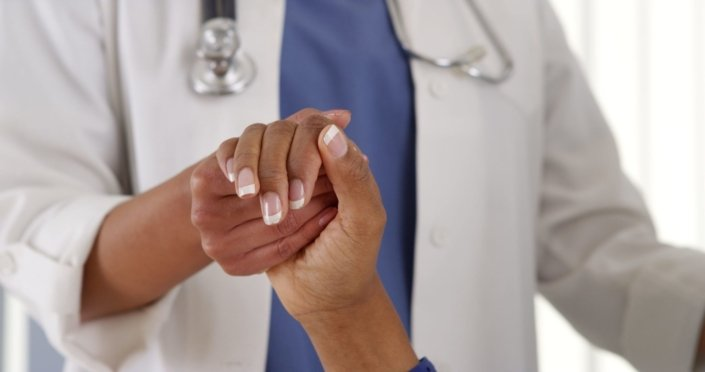 Close-up doctor holding female patient's hand