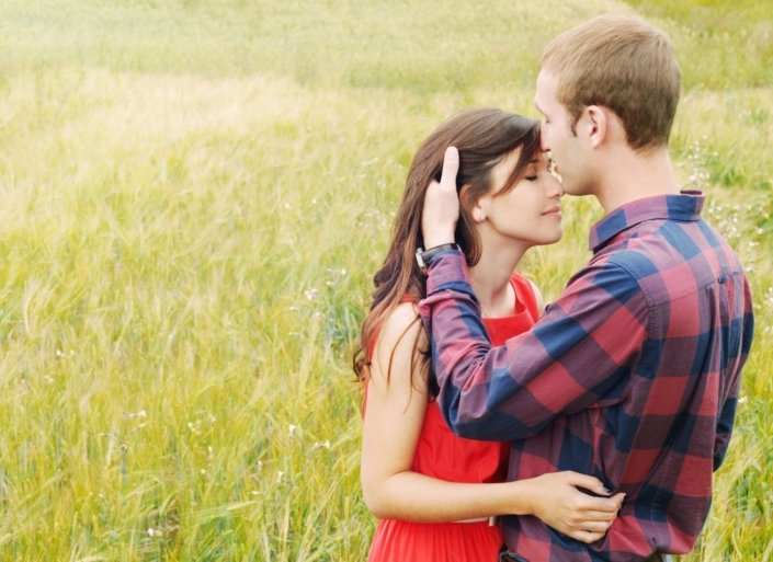 sensual outdoor portrait of young attractive couple in love kissing in summer field