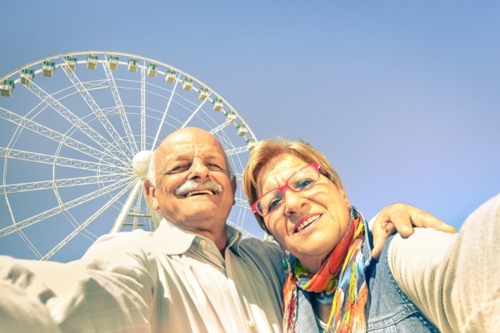 "A senior couple taking a ""selfie"" in front of a Ferris wheel"