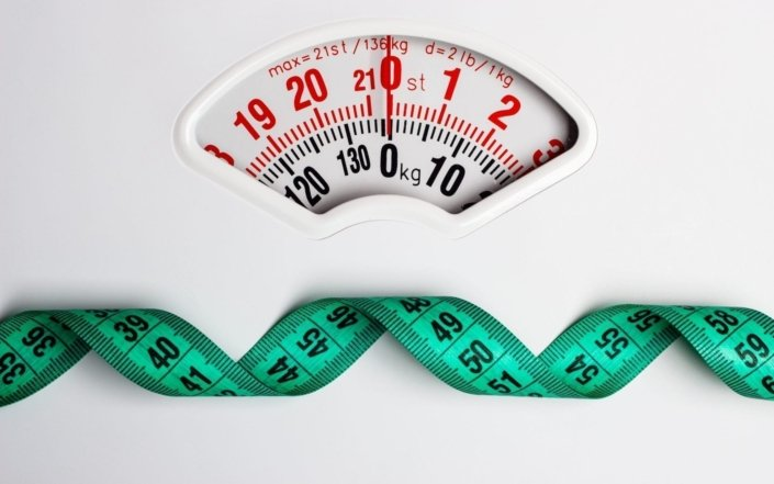 closeup measuring tape on white weight scale