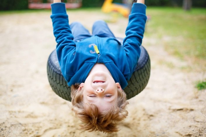 Preschool boy playing on a tire swing, leaning back as far as he can