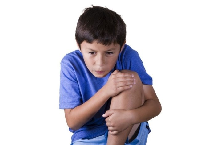 A young boy wearing a blue shirt holding leg in pain
