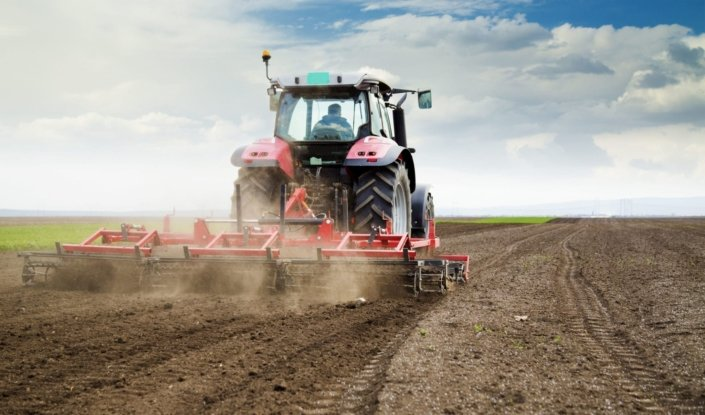 A red tractor plowing a field